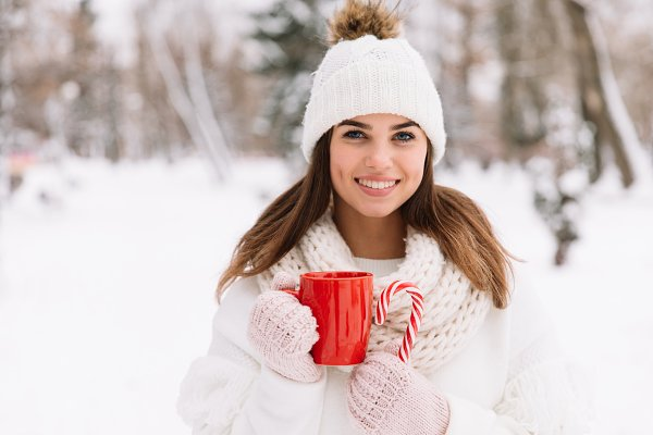 Woman holding winter cup and candy