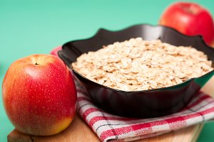 apple  with oat flakes in bowl