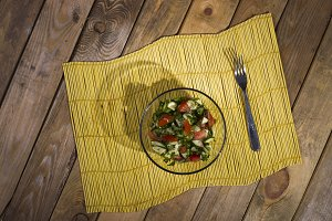 Salad on a yellow bamboo mat on wood