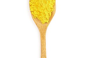 Turmeric powder in a wooden spoon