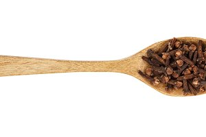 dry spice cloves in wooden spoon