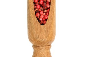red peppercorns seeds in wooden