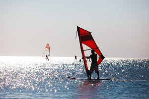 Windsurfers in the sea during sunset