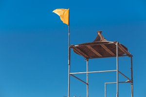 A yellow flag flies from a tall life