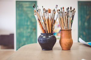 A bunch of art brushes standing in c