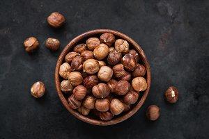 Hazelnuts in bowl on black backgroun