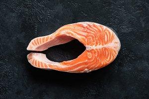 Fresh raw salmon steak on black conc