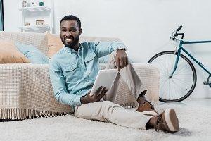 african american man sitting on floo