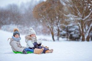 Adorable little happy girls sledding