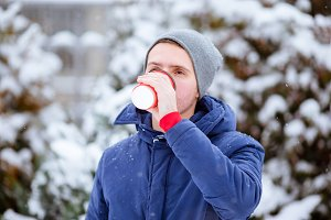 Happy man drinking coffee outdoors i