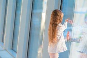 Little girl in airport near big wind
