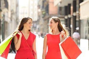 Happy shoppers talking walking in
