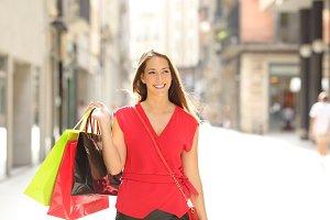 Happy shopper walking holding bags