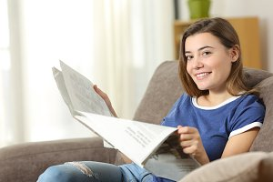 Teen reading a newspaper looking at