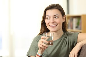 Teen holding a water glass looking