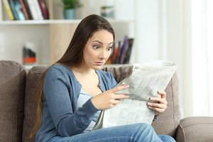 Upset woman reading surprising news