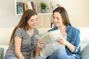 Two friends reading newspaper