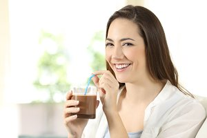 Woman drinking cocoa shake looking