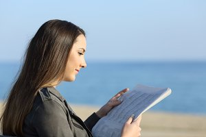 Woman relaxing reading a newspaper
