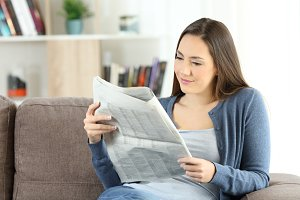 Woman reading a newspaper sitting
