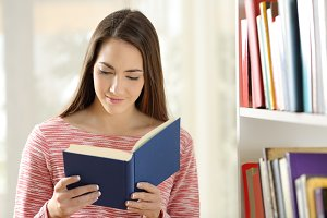 Woman reading book standing at home