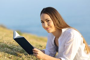 Woman reading a book looking at you