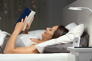 Woman reading a book in the night