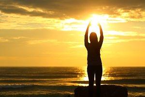 Woman reaching sun at sunset