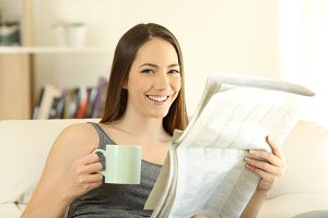 Woman holding newspaper and coffee