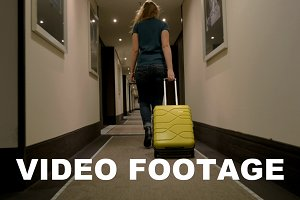 Woman with suitcase walking in hotel