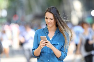 Confused woman checking phone