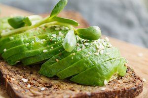 Toast with avocado on a wooden board