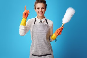 smiling housemaid with dust cleaning