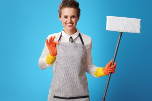 smiling young cleaning lady in apron