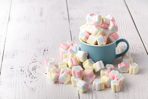 Colorful marshmallows in a cup, over