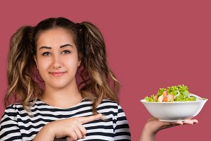 Girl pointing to the bowl of salad
