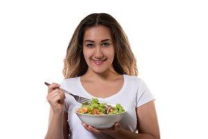 Young girl eating a fresh salad