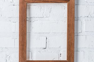 brown empty frame hanging on white b