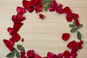 frame red roses petals on wooden