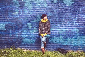 Girl leaning against blue wall