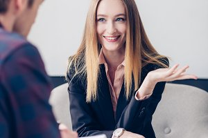smiling businesswoman in suit giving