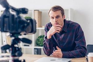 handsome pensive male video blogger