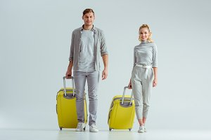 smiling couple carrying yellow suitc