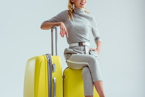 smiling woman sitting on suitcases w