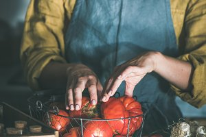 Woman in linen apron taking tomatoes