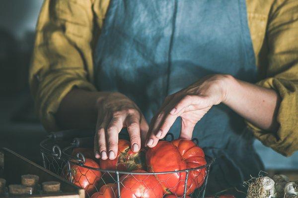 Woman in linen apron taking tomatoe…