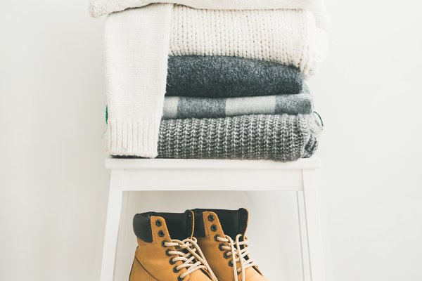 Pile of warm sweaters, blankets, ca…