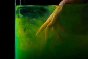 male hand in water with green paint