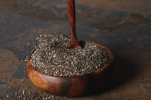 chia seeds with spoon in wooden bowl