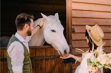 stylish newlyweds hugging near horse by  in Beauty & Fashion